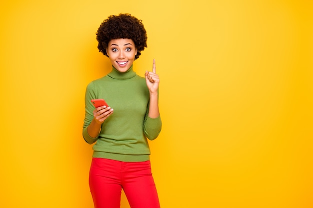 Portrait of cheerful positive cute pretty woman pointing up near empty space forefinger in red pants coming up with creative idea.