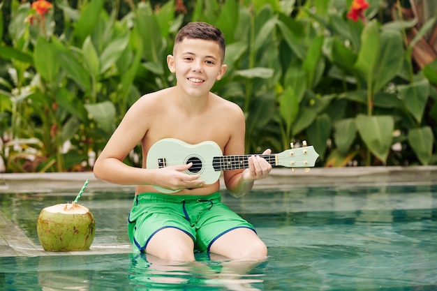 Portrait of cheerful preteen boy sitting on edge of swimming pool, playing ukulele and smiling at camera