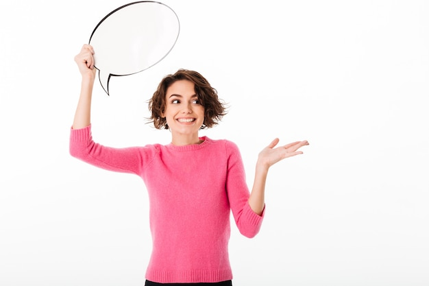 Portrait of a cheerful pretty girl holding blank speech bubble