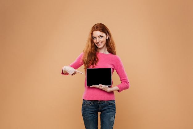 Portrait of a cheerful pretty redhead girl pointing at digital tablet