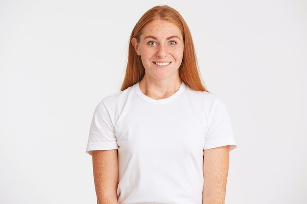 Portrait of cheerful pretty redhead young woman with long hair and freckles wears t shirt