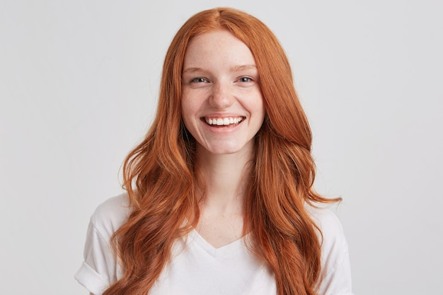Portrait of cheerful pretty redhead young woman with long wavy hair and freckles