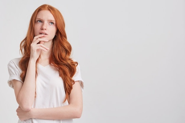 Portrait of cheerful pretty redhead young woman with long wavy hair