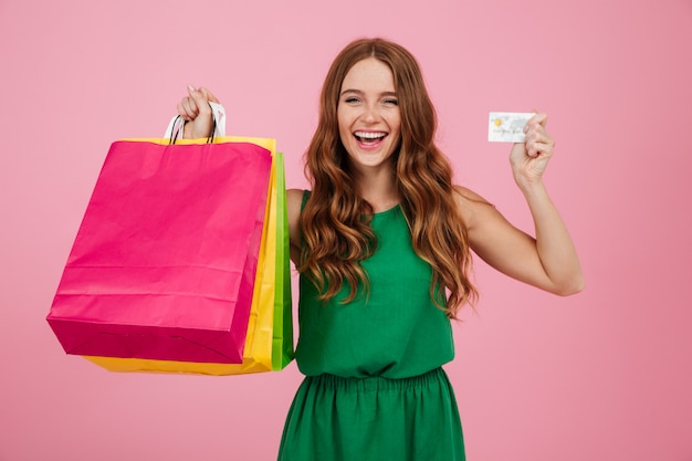Portrait of a cheerful pretty woman showing shopping bags