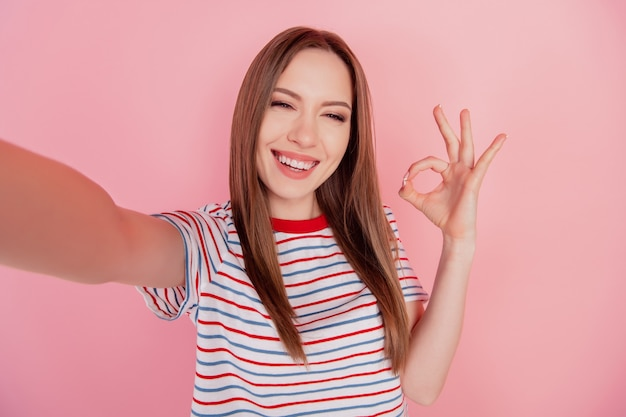 Portrait of cheerful reliable adviser lady make selfie show okey sign on pink background