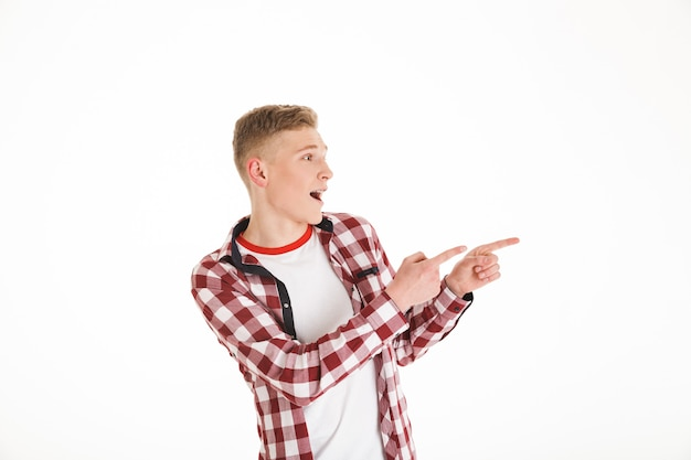 Portrait of a cheerful schoolboy pointing fingers away