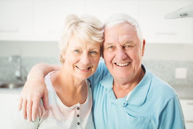 Portrait of cheerful senior couple in kitchen