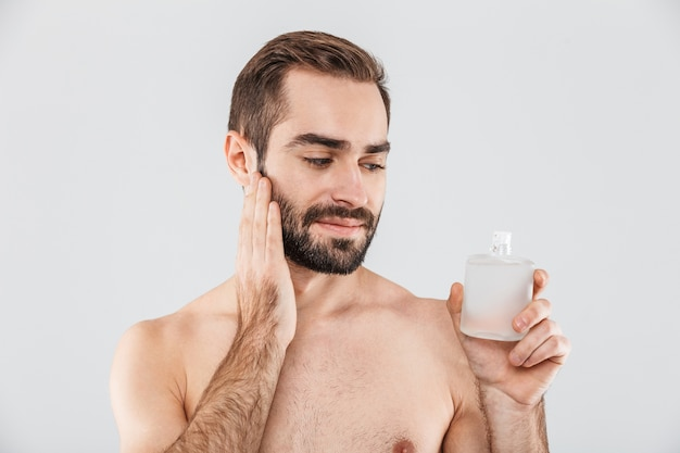 Portrait of a cheerful shirtless bearded man applying aftershave lotion isolated over white