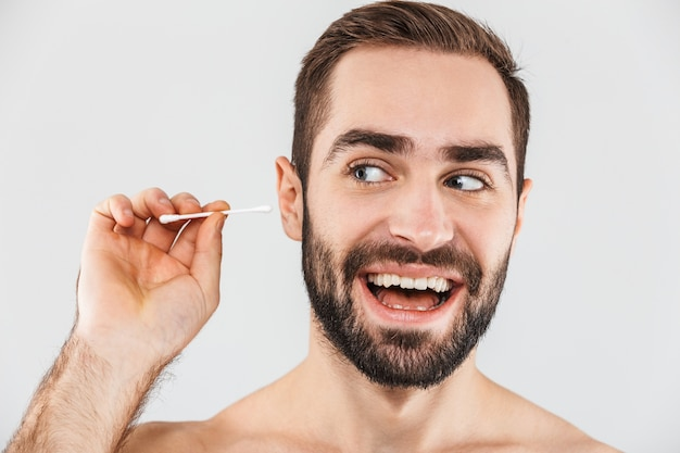 Portrait of a cheerful shirtless bearded man standing isolated over white, using cotton swab