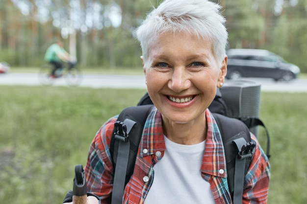 Portrait of cheerful short haired mature female hitchhiker carrying backpack and sleeping mat posing outdoors with high road and cars in background, going to spend vacations in wild nature