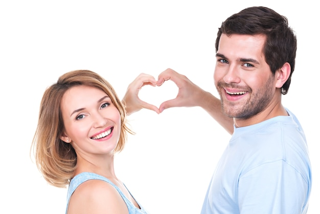 Portrait of cheerful smiling couple standing together show hands heart -  isolated