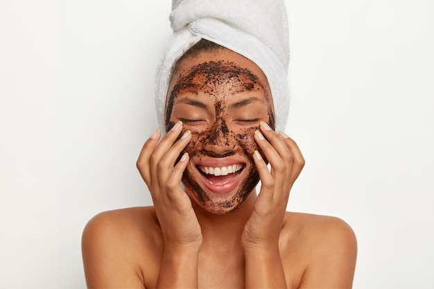 Portrait of cheerful smiling dark skinned woman applies natural coffee mask, makes circular motions with hands and massages skin, stimulates facial blood supply, wears wrapped towel on head. Free Photo