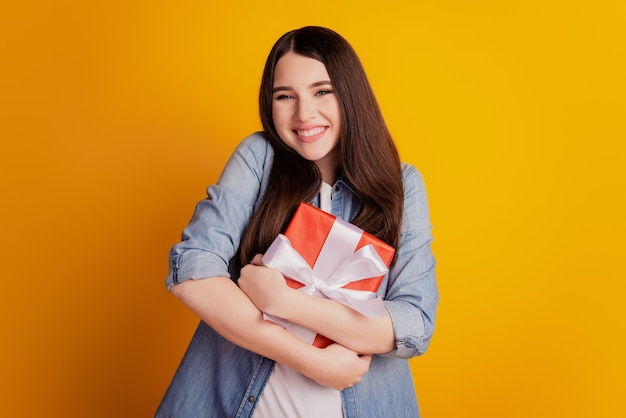 Portrait of cheerful smiling fashion girl embrace present box on yellow background