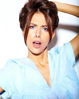 Ritratto di donna allegra sorridente moda impazzendo in abiti estivi casual blu hipster senza trucco sul muro bianco