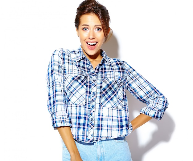 Portrait of cheerful smiling fashion woman going crazy in casual  hipster checkered shirt with no makeup on white wall