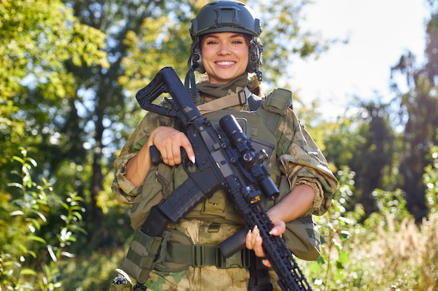 Portrait of cheerful smiling female soldier with rifle gun in hands in green military suit and hat