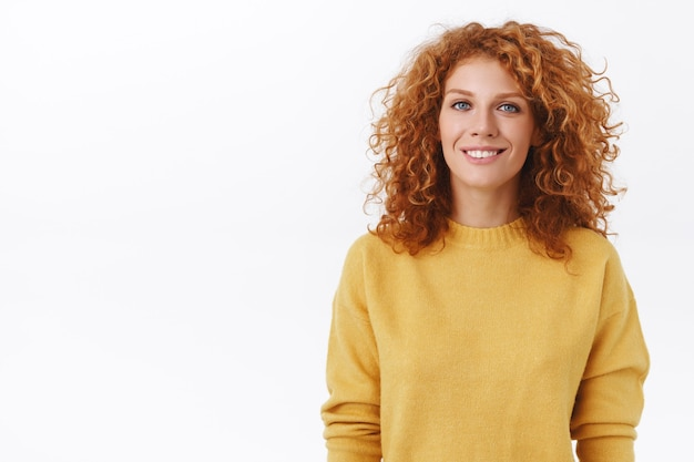 Ritratto allegro, sorridente felice donna rossa con capelli ricci in maglione giallo, sogghignando e guardando la macchina fotografica con espressione amichevole e gioiosa, concetto di stile di vita ed emozioni, muro bianco