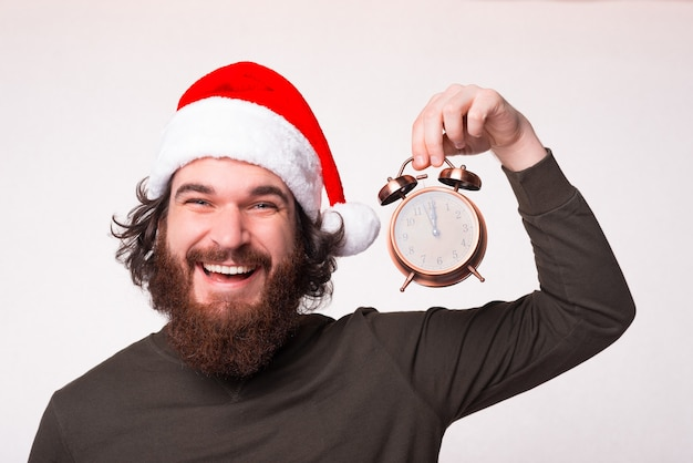 Portrait of cheerful smiling man with beard wearing santa claus hat and holding alarm clock