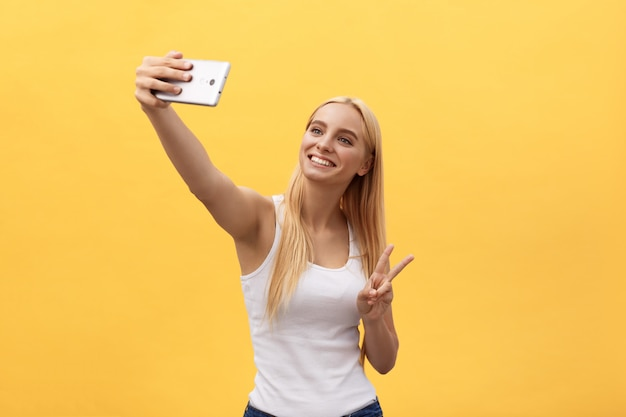 Portrait of a cheerful smiling woman in white shirt taking selfie isolated on yellow background