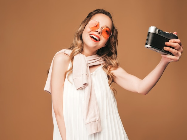 Portrait of cheerful smiling young woman taking photo selfie with inspiration and wearing white dress. girl holding retro camera. model in sunglasses posing