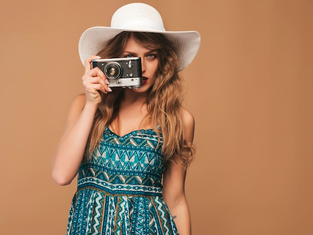 Portrait of cheerful smiling young woman taking photo with inspiration and wearing summer dress. girl holding retro camera. model posing in hat
