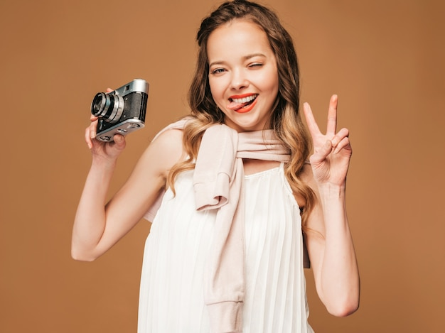 Portrait of cheerful smiling young woman taking photo  with inspiration and wearing white dress. girl holding retro camera. model posing, showing peace sign