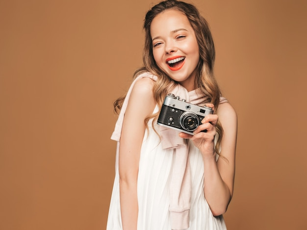 Portrait of cheerful smiling young woman taking photo  with inspiration and wearing white dress. girl holding retro camera. model posing