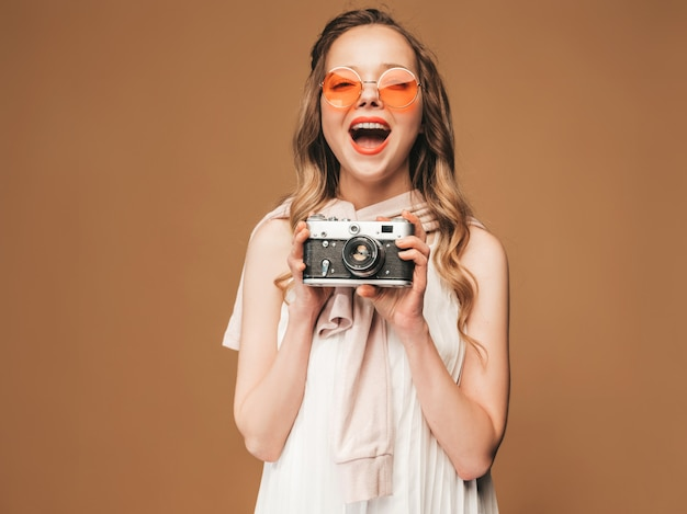 Portrait of cheerful smiling young woman taking photo  with inspiration and wearing white dress. girl holding retro camera. model in sunglasses posing