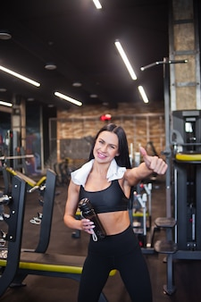 Portrait of a cheerful smilling young sportswoman showing thumb up in gym
