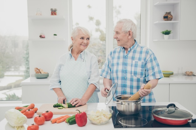 Portrait of cheerful spouses cooking