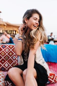 Ritratto di ragazza dai capelli lunghi alla moda allegra divertendosi sulla festa all'aperto con gli amici
