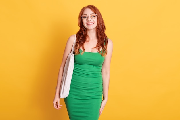 Portrait of cheerful stylish trendy attractive red haired female wearing green dress