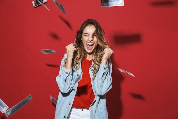 Portrait of a cheerful stylish young woman wearing denim jacket standing isolated over red wall, standing under money banknotes rain