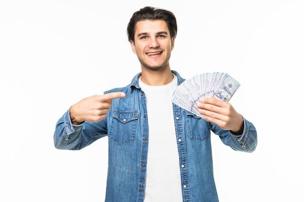 Ritratto di un allegro uomo di successo in camicia bianca che mostra un mucchio di banconote in due mani mentre sta in piedi e celebra isolato su bianco