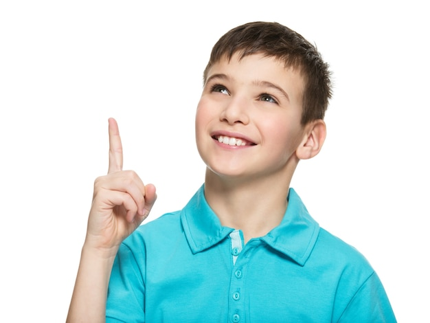 Portrait of the cheerful teen boy pointing finger up -  isolated over white