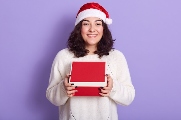 Portrait of cheerful tender brunette holding box with present in both hands