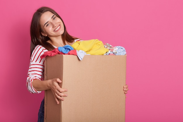 Portrait of cheerful tender female holding carton box in arms, taking items of clothes, being volunteer, having kind heart, smiling sincerely