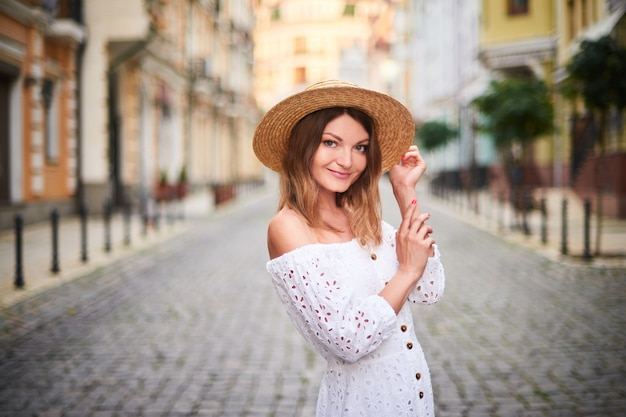 Portrait cheerful tourist woman standing on ancient street in old town