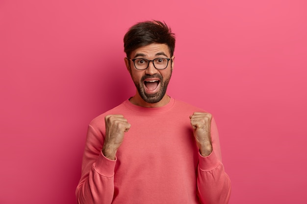Portrait of cheerful unshaven adult man clenches fists with triumph, rejoices nice moment in life, exclaims positively, wears transparent glasses and rosy jumper, celebrates victory or success