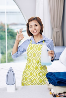 Portrait of cheerful vietnamese housewife with bottle of scented ironing water in hand showing ok sign