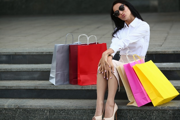 Portrait of cheerful woman blowing kiss on steps outdoors. beautiful female in stylish sunglasses posing with colorful shop bags. fashion and shopping concept.