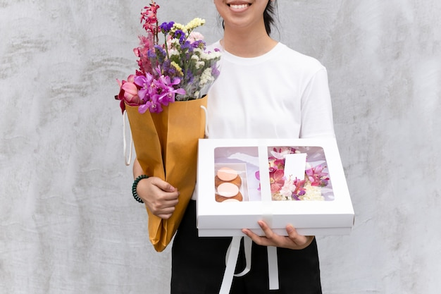Portrait of cheerful woman holding flowers and gift box.
