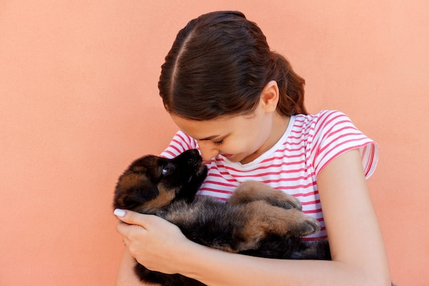 Portrait of a cheerful woman holding and looking at an adorable small puppy