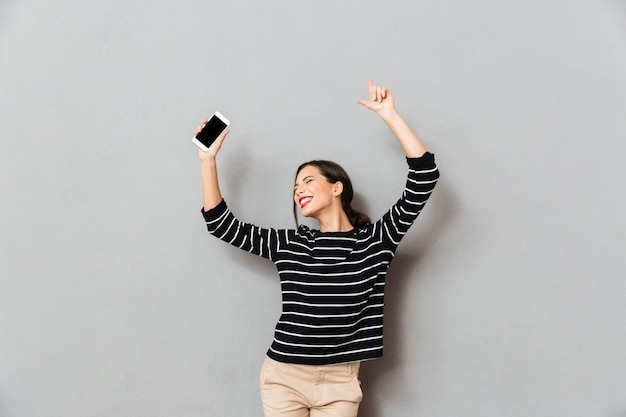 Portrait of a cheerful woman holding mobile phone
