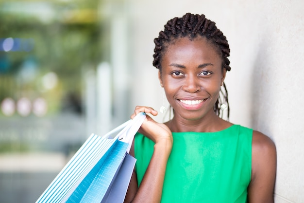Portrait of cheerful woman holding shopping bags