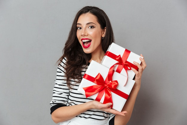 Portrait of a cheerful woman holding stack of gift boxes