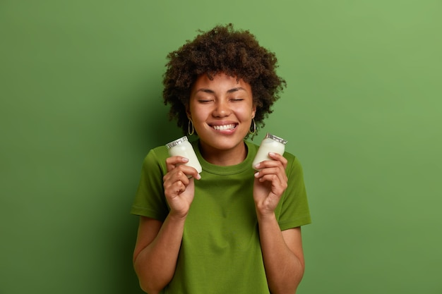 Portrait of cheerful woman holds two bottles of natural dairy yogurt for breakfast, bites lips and has temptation to eat, stands with closed eyes, isolated on green wall. healthy nutrition concept
