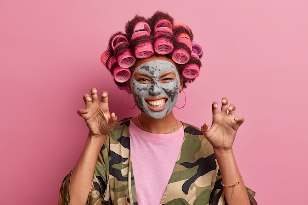 Portrait of cheerful woman makes cat claws and growls like animal, wears hair curlers on head, applies beauty clay mask, dressed casually poses against pink  has funny grimace clenches teeth