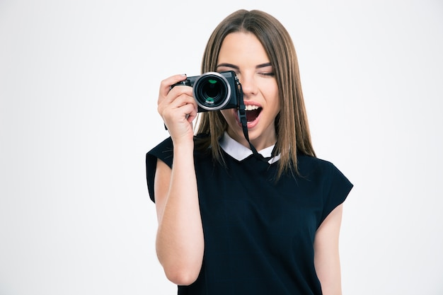 Portrait of a cheerful woman making photo on camera isolated