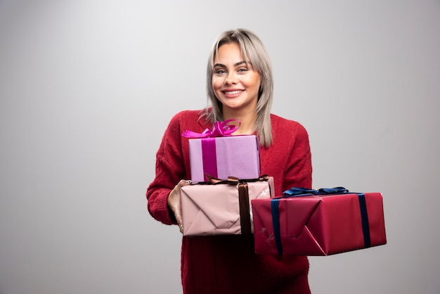 Portrait of cheerful woman offering holiday gifts on gray background.